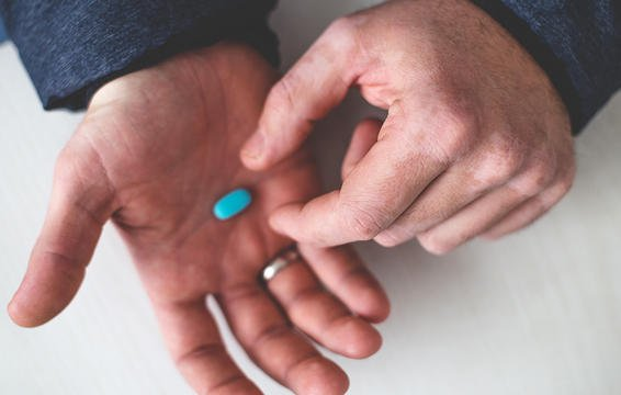 close up on man dropping a blue pill into his other hand